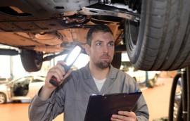 Gutachter in Autowerkstatt untersucht Fahrzeug auf Mngel