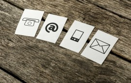 Contact and communication icons, telephone, at sign, mobile and mail, on four white cards spread over textured rustic wooden boards.